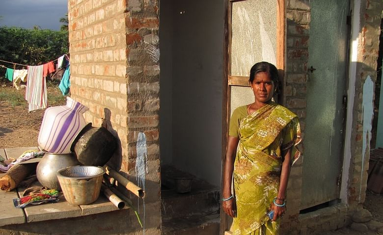 Mayula, pictured beside the toilet and bathroom, constructed with the help of her microloan