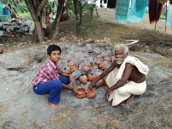 Student assisting his grandfather in pottery