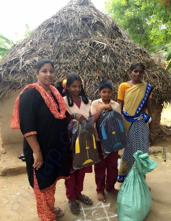 Indra with her children before her house
