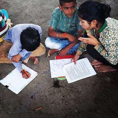 Volunteers from the village helping children in class