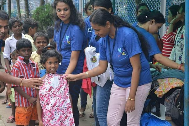 Our Team Member gifting new cloth to a girl