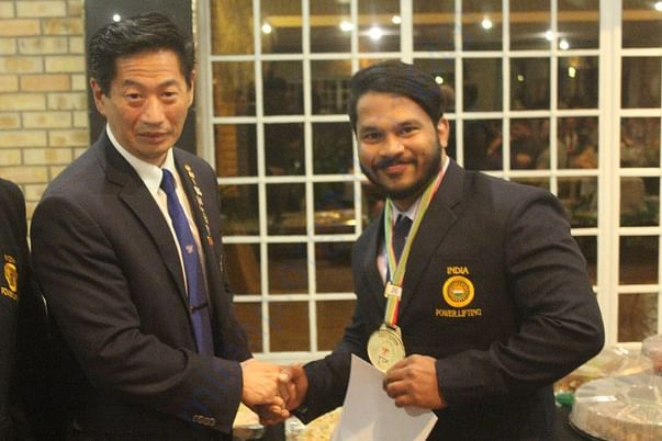 Receiving Best Lifter Award from International Officials at SA