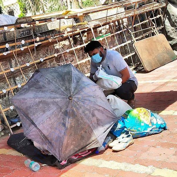 Our Aurangabad Team volunteer helping a homeless person  on street .