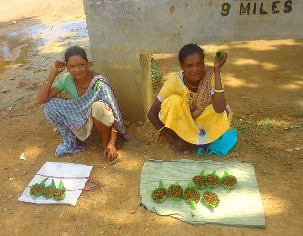 कोलई (मेफ्लाई) कीड़े को बेचती आदिवासी महिला